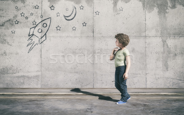The young boy standing next to grey wall Stock photo © orla