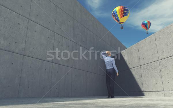 Young man looking over wall at air balloon Stock photo © orla