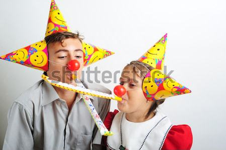 A little girl and a boy with party horn and clown noses  Stock photo © orla