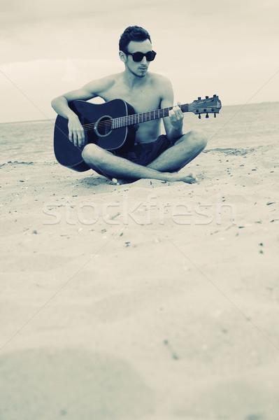 Boy playing guitar on the beach Stock photo © orla