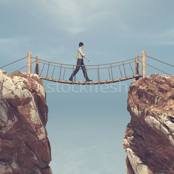 Man rope passing over a bridge suspended between mountains.  Stock photo © orla
