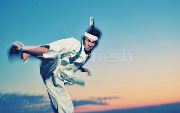 Young boy in karate uniform training at sunset  Stock photo © orla