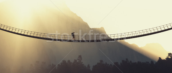Man with backpack on a rope bridge Stock photo © orla