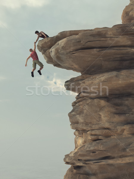 Young man holds out a hand of a climber Stock photo © orla