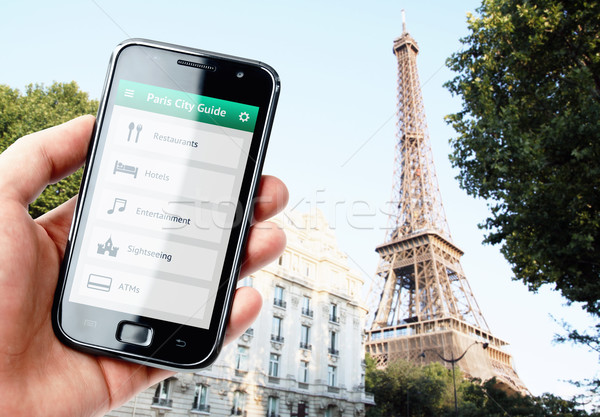 Hand holding smartphone with city guide in Paris Stock photo © pab_map
