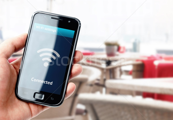 Hand holding smartphone with wi-fi connection in cafe Stock photo © pab_map