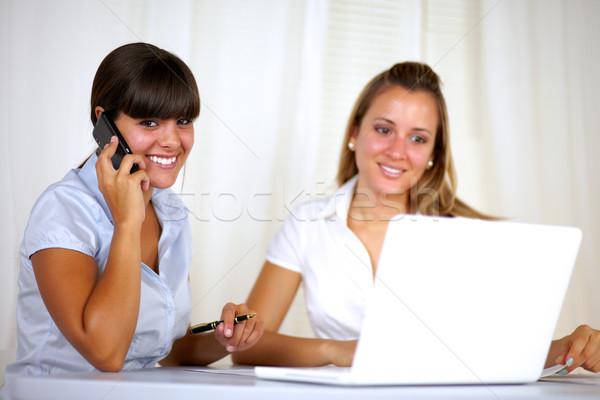 Uśmiechnięty kobieta interesu mówić młodych biuro Zdjęcia stock © pablocalvog