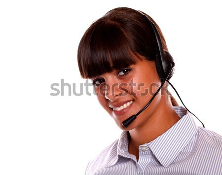 Smiling secretary using earphone looking at you Stock photo © pablocalvog