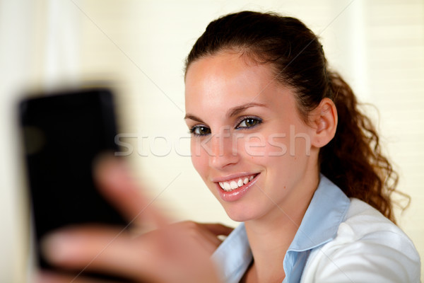 Young woman looking and smiling to cellphone Stock photo © pablocalvog