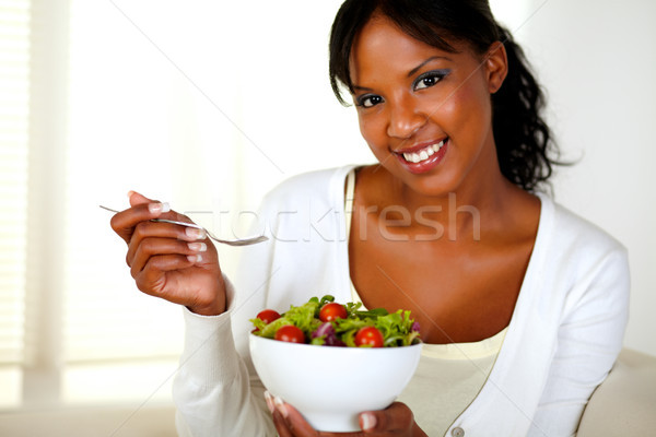 Young woman looking at you while eating salad Stock photo © pablocalvog
