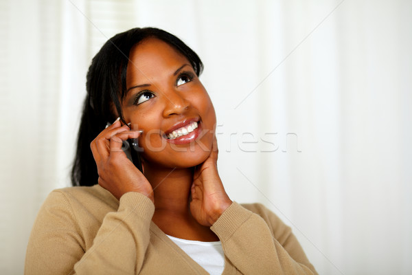 Stock photo: Charming girl looking up and conversing on mobile