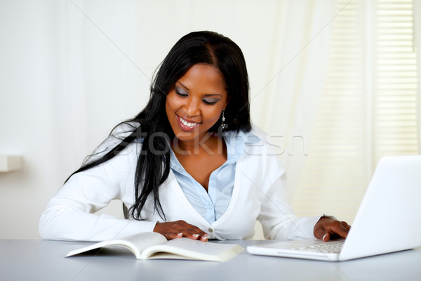 Charming student woman browsing a book Stock photo © pablocalvog