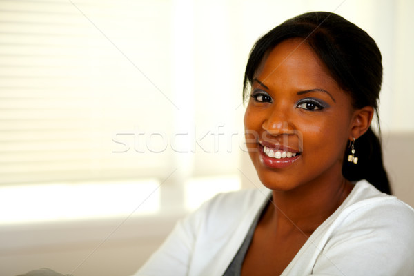 Relaxed afro-american young female smiling at you Stock photo © pablocalvog