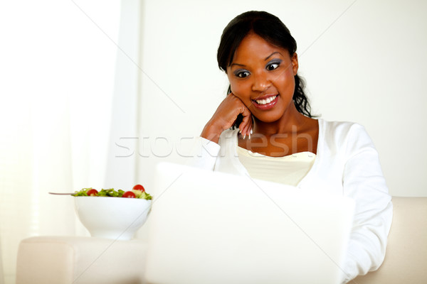 Surprised black woman eating fresh vegetable salad Stock photo © pablocalvog