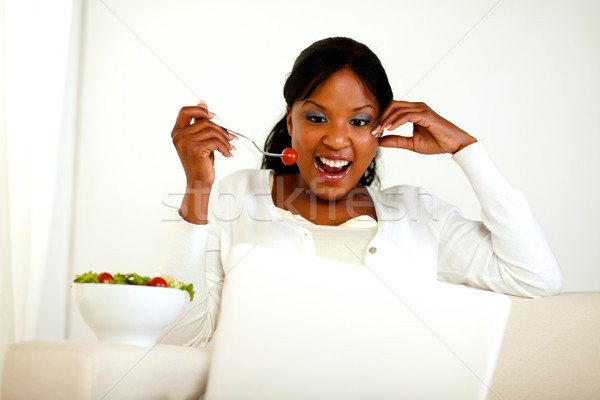 Surprised young woman eating fresh vegetable salad Stock photo © pablocalvog
