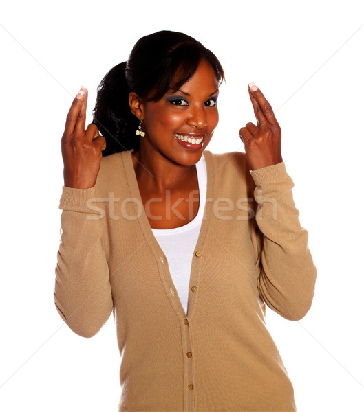 Smiling woman crossing fingers looking at you Stock photo © pablocalvog