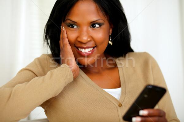 Stockfoto: Peinzend · zwarte · vrouw · mobieltje · portret · vrouw · glimlach