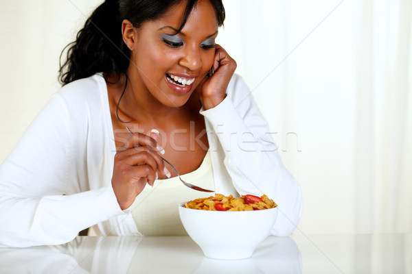 Charming young woman eating a bowl of cereals Stock photo © pablocalvog