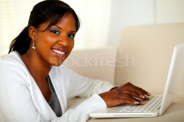 Young woman looking at you while working on laptop Stock photo © pablocalvog