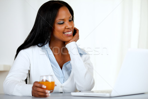 Afro-american young woman looking to laptop screen Stock photo © pablocalvog
