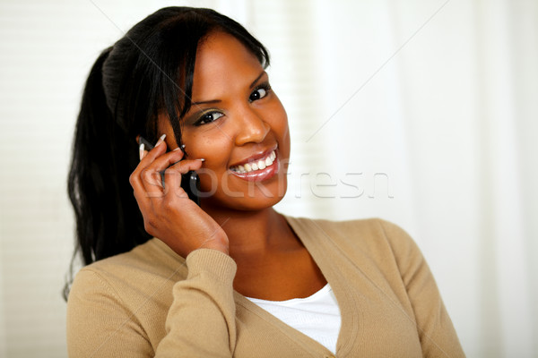 Stock photo: Relaxed woman smiling at you with a cellphone
