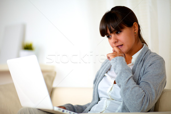 Reflective young woman reading the laptop screen Stock photo © pablocalvog