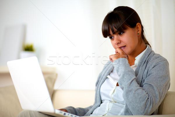 Réfléchissant jeune femme lecture portable écran portrait Photo stock © pablocalvog