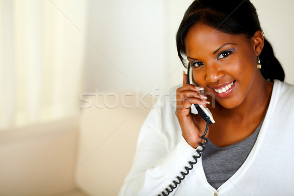 Smiling black woman looking at you while talking Stock photo © pablocalvog