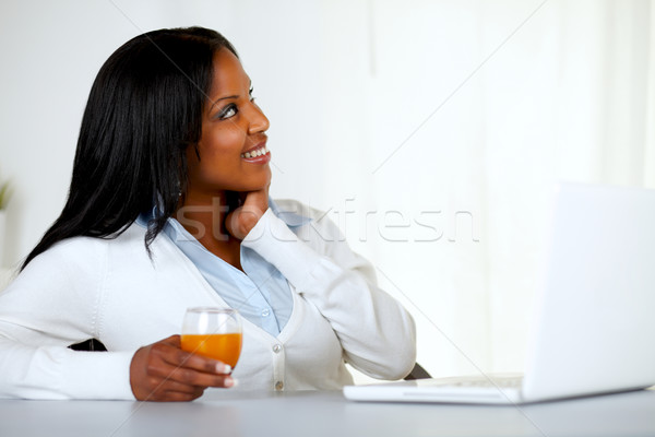 Pretty young woman looking up with an orange juice Stock photo © pablocalvog