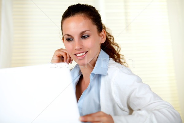 Smiling young woman browsing the internet Stock photo © pablocalvog
