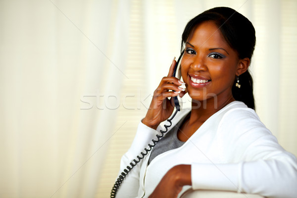 Charming young woman smiling at you on phone Stock photo © pablocalvog