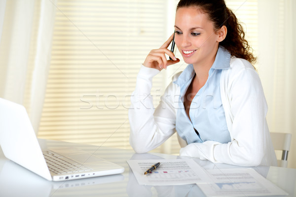 Smiling businesswoman conversing on cellphone Stock photo © pablocalvog