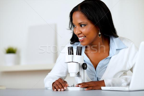 Pretty black female working with a microscope Stock photo © pablocalvog