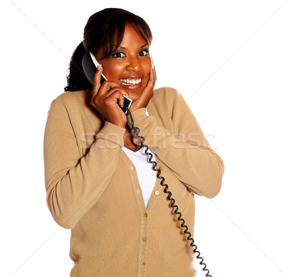 Stock photo: Happy young woman smiling and conversing on phone
