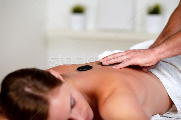Young woman getting a massage with hot stones Stock photo © pablocalvog