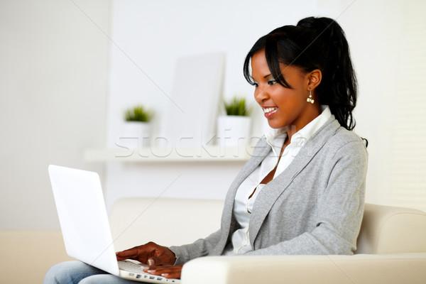 женщину используя ноутбук портрет сидят диван домой Сток-фото © pablocalvog