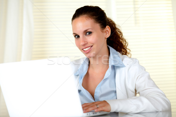 Smiling young woman looking at you with laptop Stock photo © pablocalvog