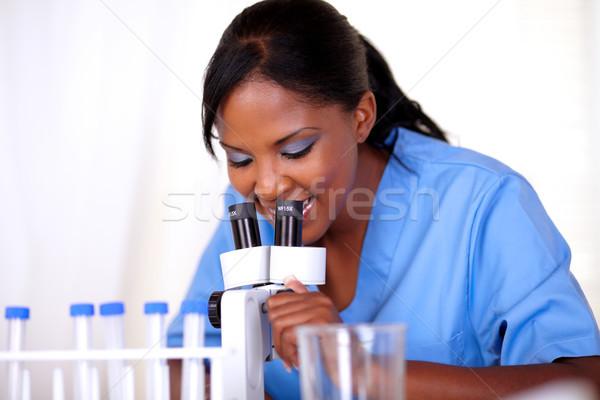 Tudományos lány kék egyenruha mikroszkóp laboratórium Stock fotó © pablocalvog
