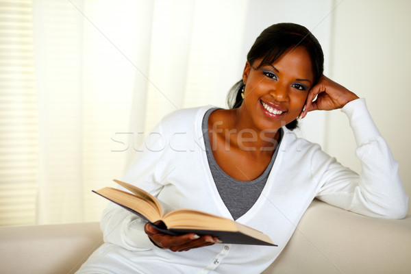 Young woman looking at you while holding a book Stock photo © pablocalvog