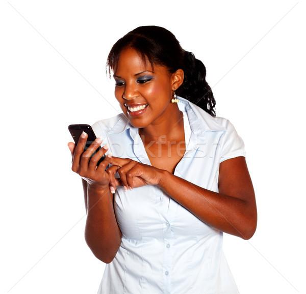Fiatal nő küldés üzenet mobiltelefon izolált mosoly Stock fotó © pablocalvog