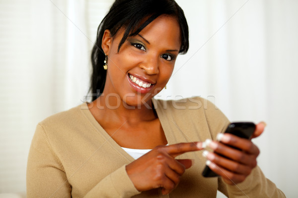 Woman pointing her cellphone and smiling at you Stock photo © pablocalvog