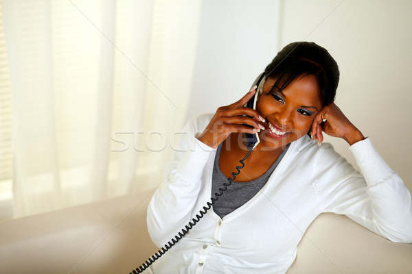 Relaxed black girl smiling and conversing on phone Stock photo © pablocalvog