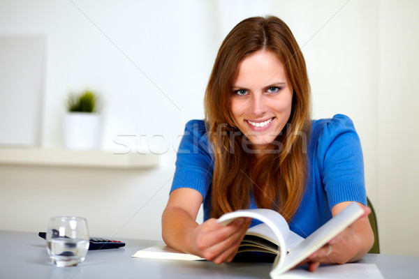Lovely young woman smiling and reading a book Stock photo © pablocalvog