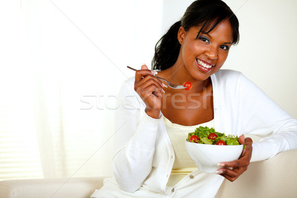 Black woman looking at you as she eats her salad Stock photo © pablocalvog