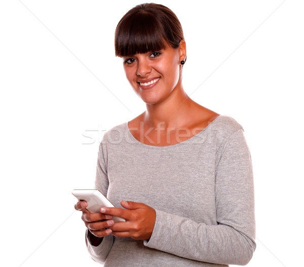 Pretty young female looking at you using cellphone Stock photo © pablocalvog