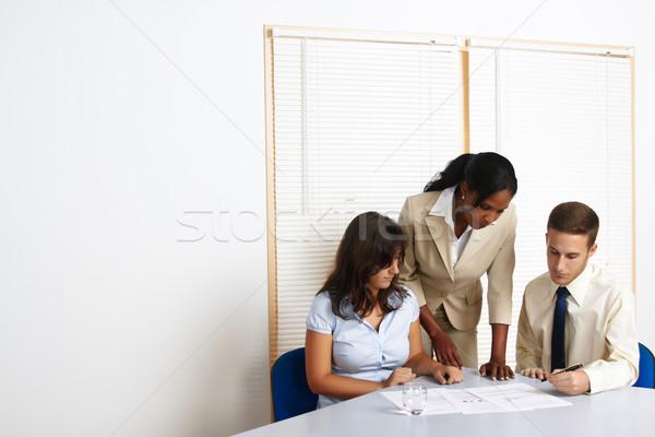Jovem pessoas de negócios trabalhando multinacional grupo documentos Foto stock © pablocalvog