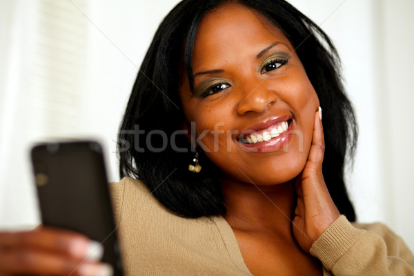 Young woman smiling at you while sending a message Stock photo © pablocalvog
