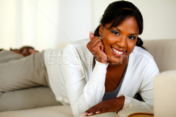 Smiling woman looking at you while lying on sofa Stock photo © pablocalvog