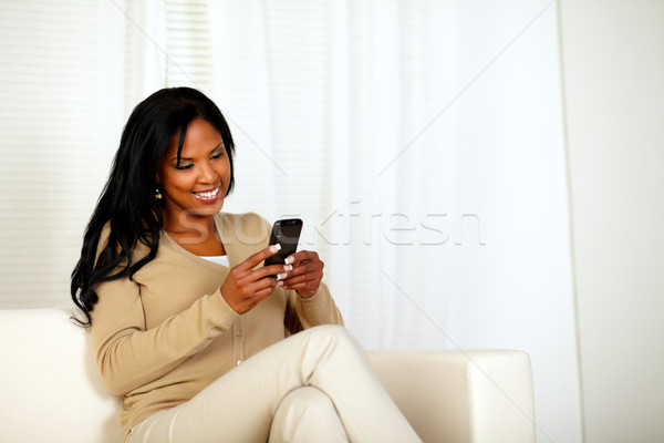 Stock photo: Black woman sending a message by the cellphone
