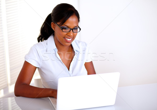 Stock photo: Young pretty businesswoman working on laptop